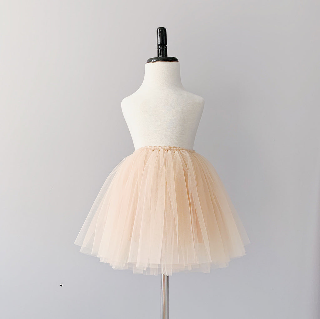 Bluish Baby Celine Tutu Skirt in cream colour. It is made with three layers of silky soft tulle, a layer of cotton lining, and a velvety waistband that hugs your child's waist. Ethically made in China, and the finishing touches are done by hand in Toronto, Canada.