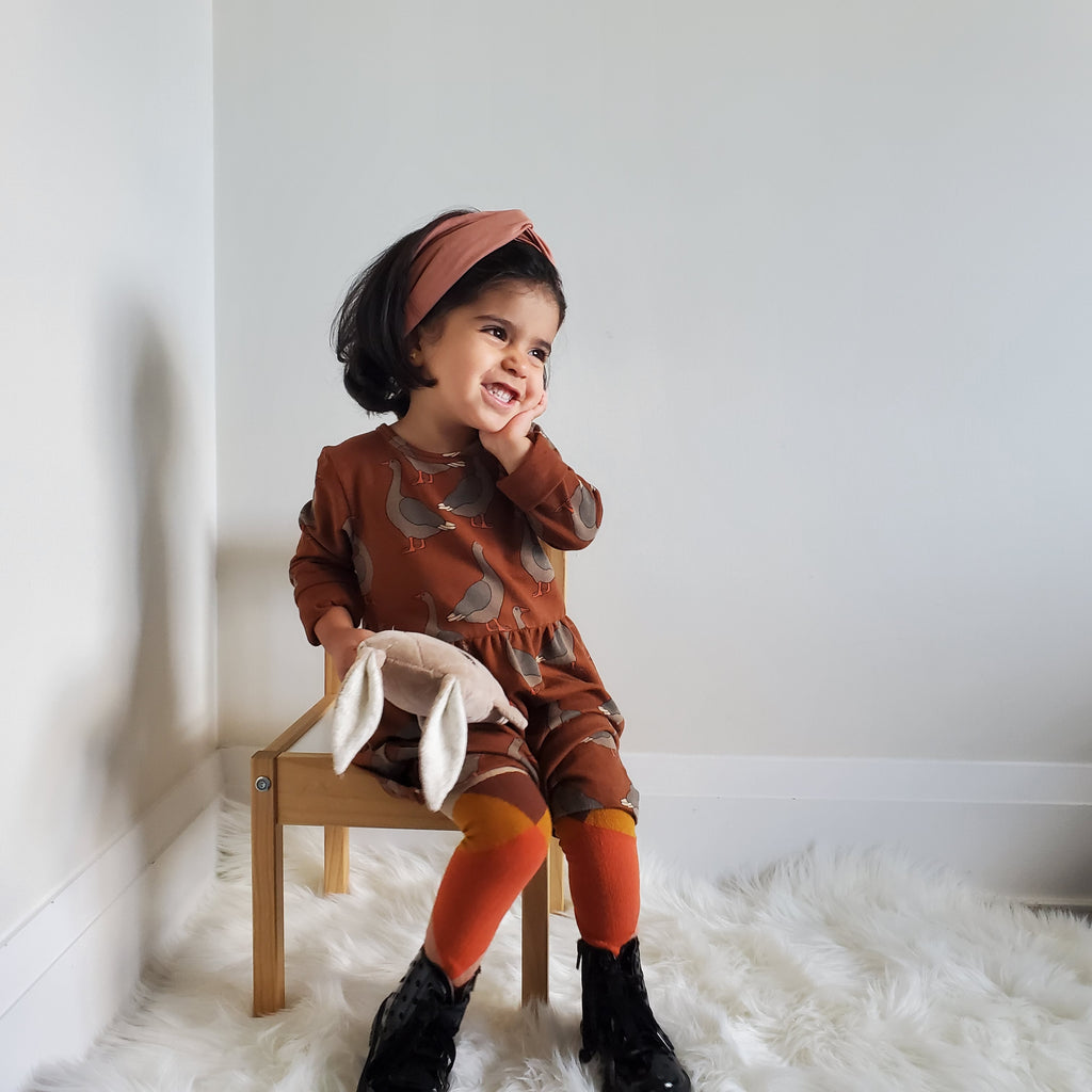 Girl wearing Carlijnq dress made of 48% Organic Cotton / 48% Modal / 4% Elastane. Brown, with long sleeves and all-over goose print.