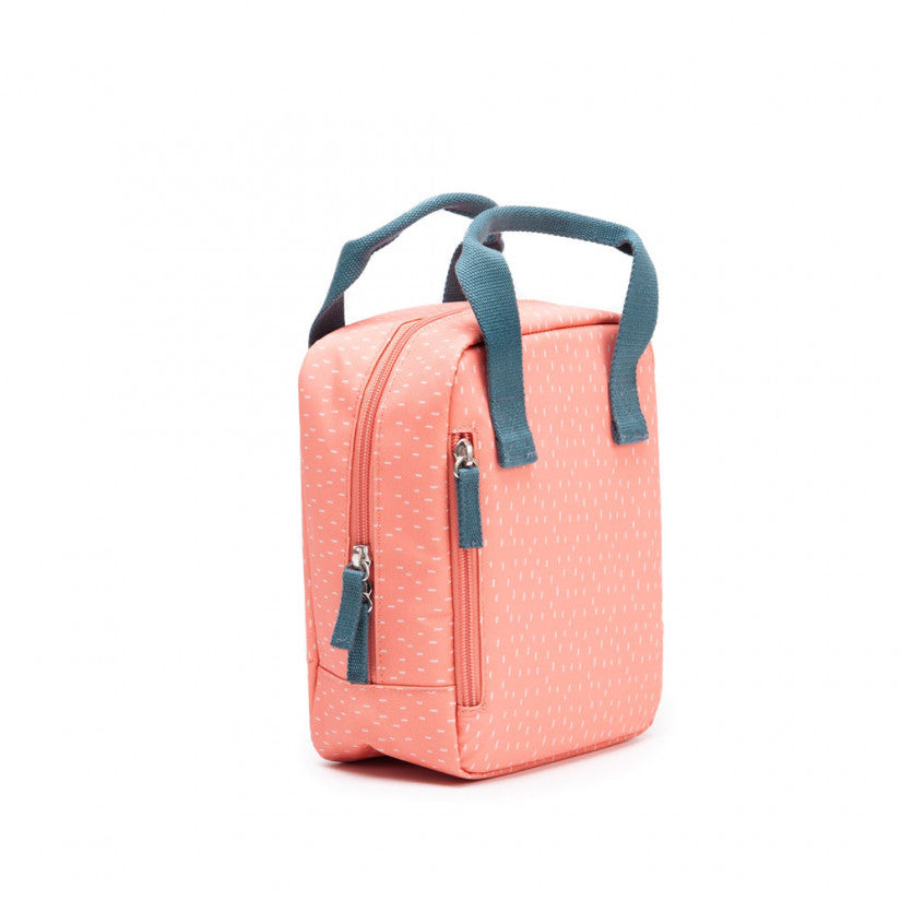 Ekobo insulated lunch bag in pink with white dots, and green handle.