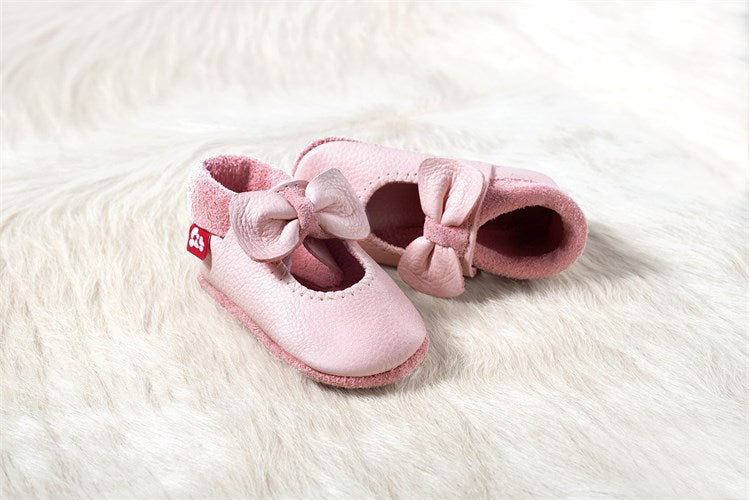 Soft leather infant shoes in pink, with a bow at the front. Made with eco-friendly materials and dyes.