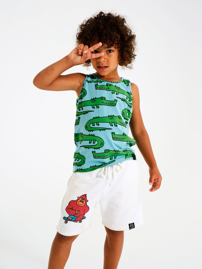 Kid wearing Kukukid white Monkey Pocket Shorts. Ethically made in Poland.