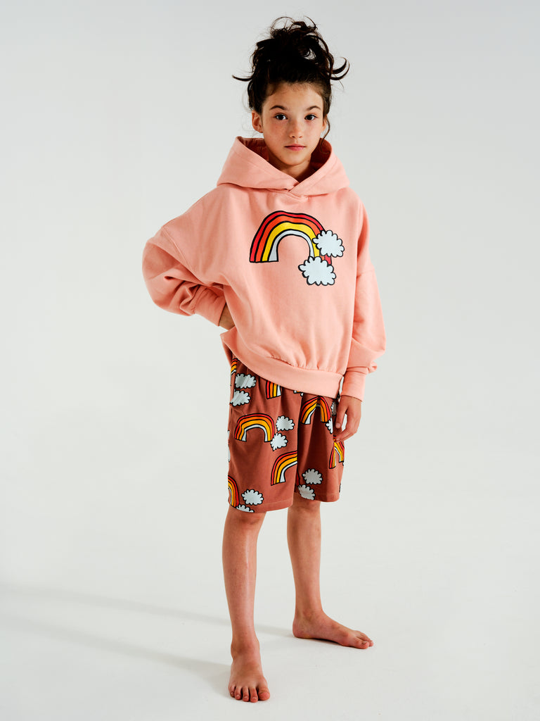 Girl wearing Kukukid oversized hoodie with rainbow print at the front. Ethically made in Poland.