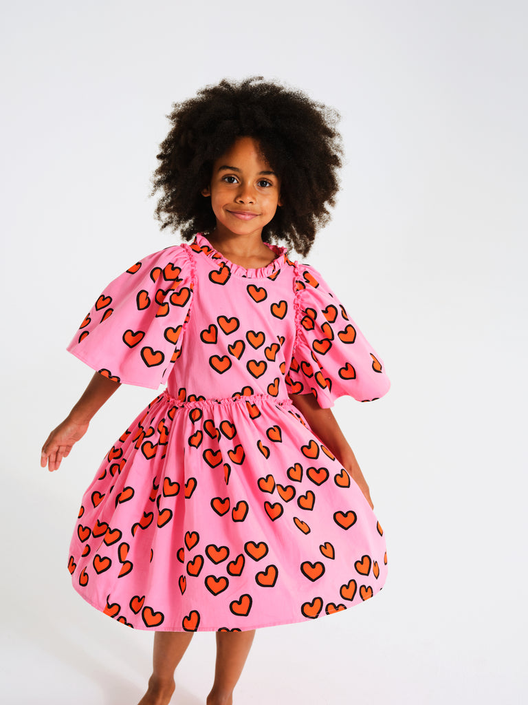 Kukukid cape dress in bright pink with red hearts print all over. Ethically made in Poland.