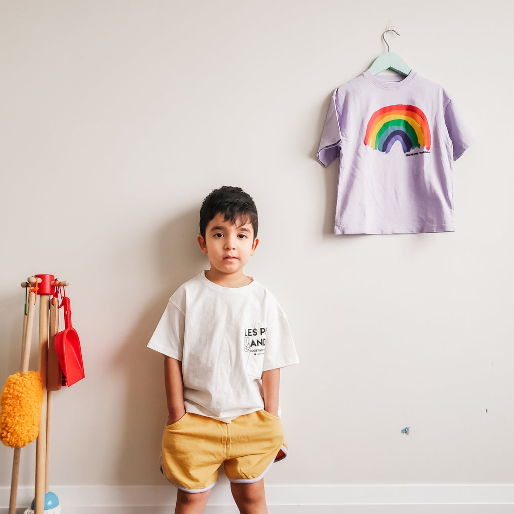 Boy modelling Les petits vandales pocket t-shirt and rainbow shorts.