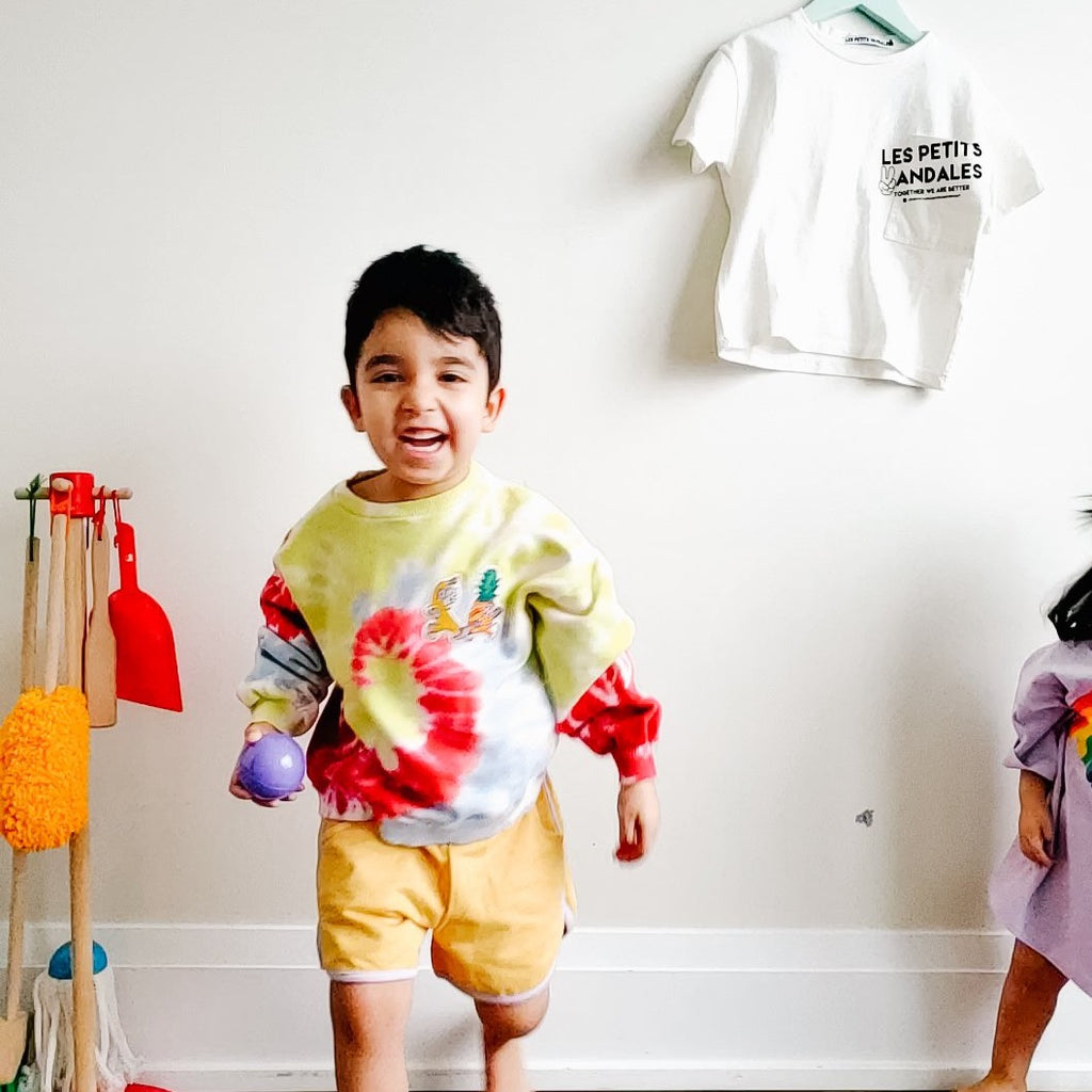 Boy modelling Les petits vandales tie dye kids sweatshirt, with a banana and pineapple patches at the front. Made with recycled cotton in Portugal.