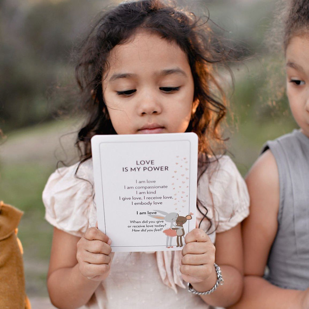 Girl reading her Love Powered Affirmation Cards
