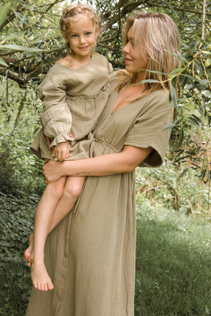 Mama and daughter wearing Ammehoela One size fits-all. well most! Thanks to the cut of this dress moms from all sizes can fit in one size. Drop-down shoulders, deep v-neck, and an elasticated waistband that could go from XS to XL. Made ethically in Turkey with 100% cotton.