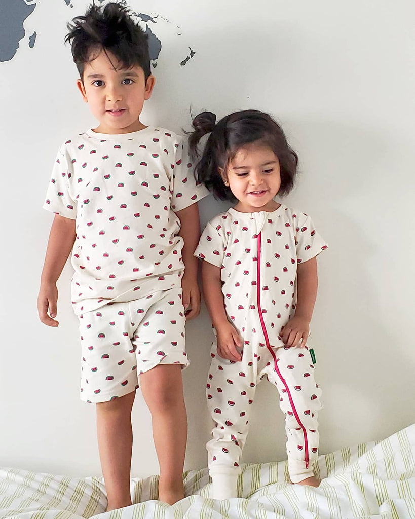 Parade Organics Summer collection. Boy wearing a two piece summer pyjama, and a girl wearing a two-way-zipper romper in blue with watermelon prints.
