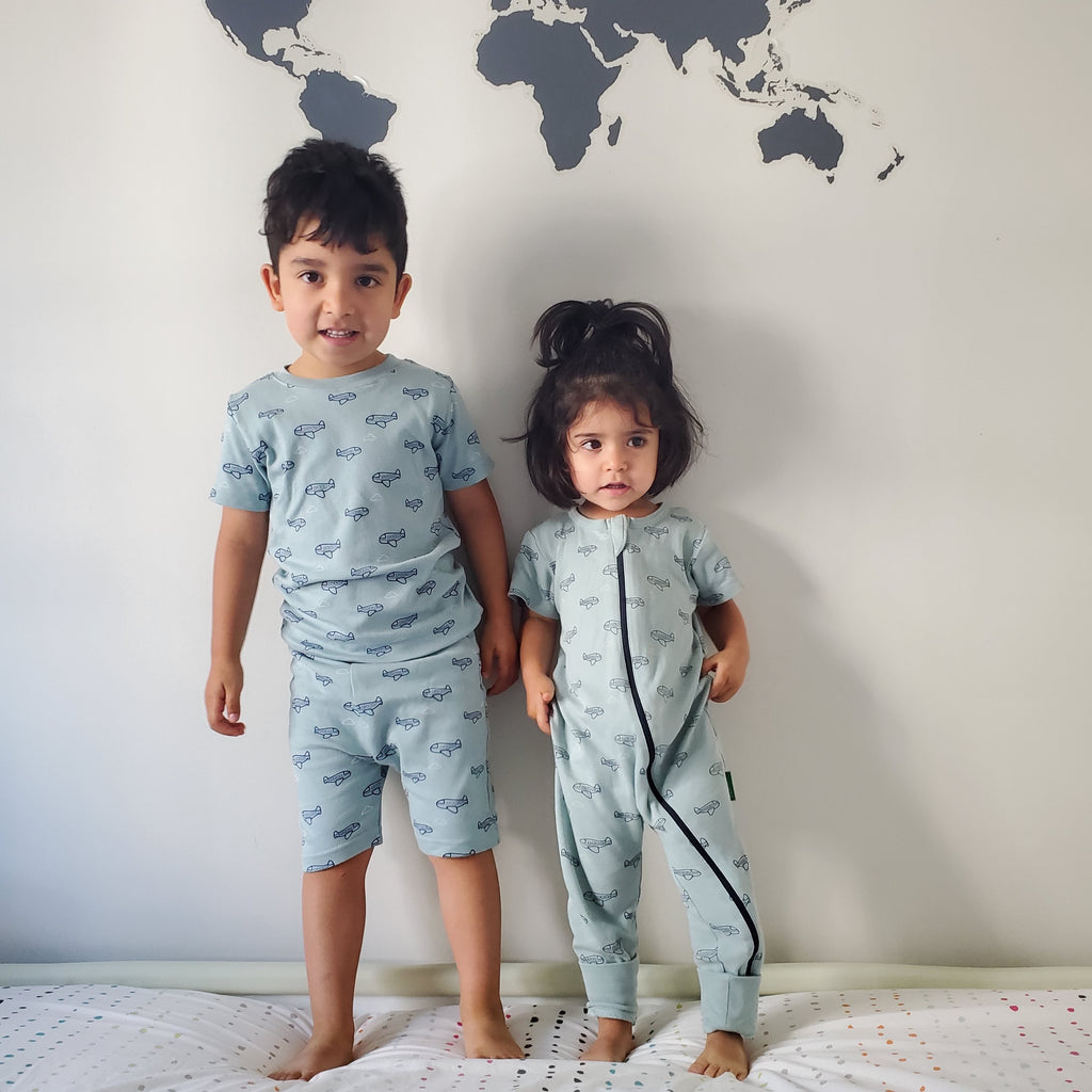 Parade Organics Summer collection. Boy wearing a two piece summer pyjama, and a girl wearing a two-way-zipper romper in blue with airplane prints.