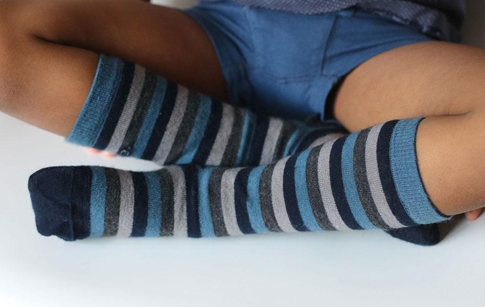 Boy wearing Q for Quinn  merino wool socks, made from ZQ certified merino wool. Blue and grey stripes.
