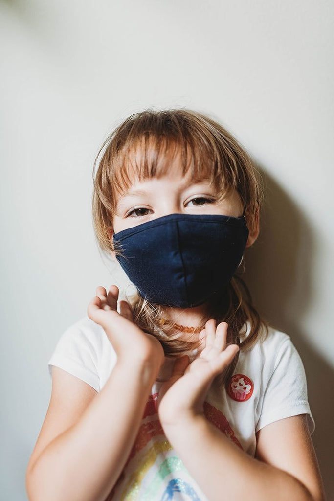 Girl wearing Q for Quinn black cotton masks, made ethically in India with 100% organic cotton.