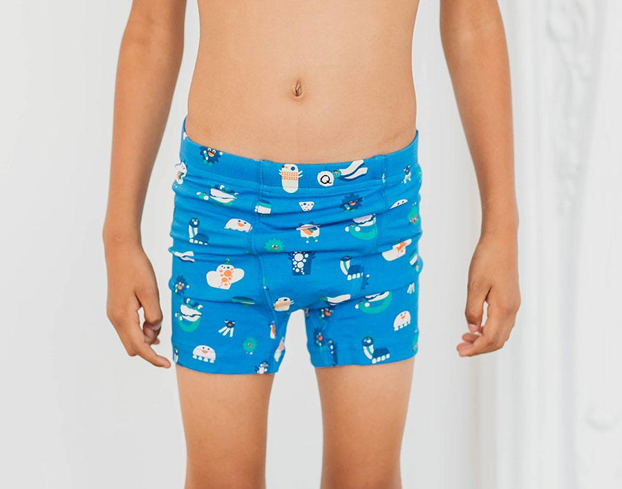 Boy wearing Q for Quinn organic underwear for boys.  Funny creatures  print, in blue and orange. Made ethically in India.