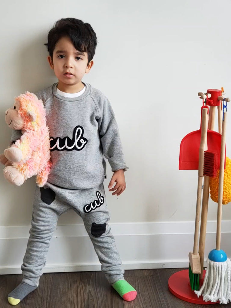 Boy wearing Tobias and the Bear kids Cub grey joggers are ethically made in the UK with 100% organic cotton. Modern styles without compromising comfort. Gender neutral kids fashion.