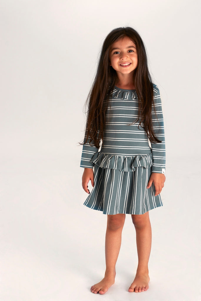 Girl wearing Turtledove London jersey dress. Ethically made in India from GOTS certified organic cotton jersey, the soft fabric is inserted as frills to neck and waist for a pretty finish. Stripe option in new Steel colourpop is a contemporary choice for 0-6 years.