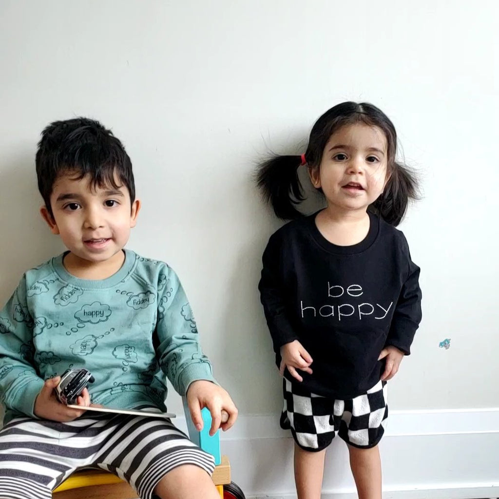 Girl wearing Turtledove London embroidered Be Happy sweatshirt in back. Made of 100% GOTS certified cotton. Gender neutral kids clothes.