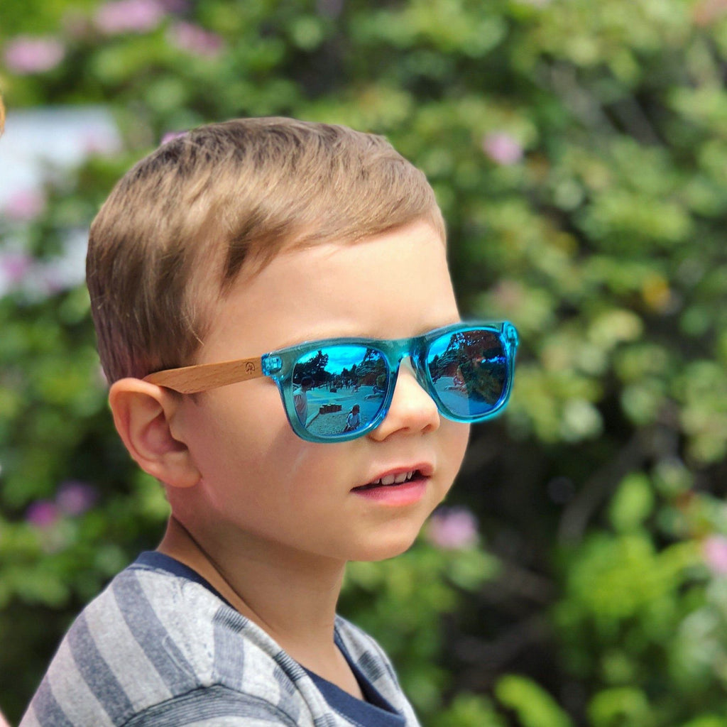 Kid wearing Wildwood kids' polarized sunglasses with recycled plastic frames and solid beech wood arms. Colour blue.