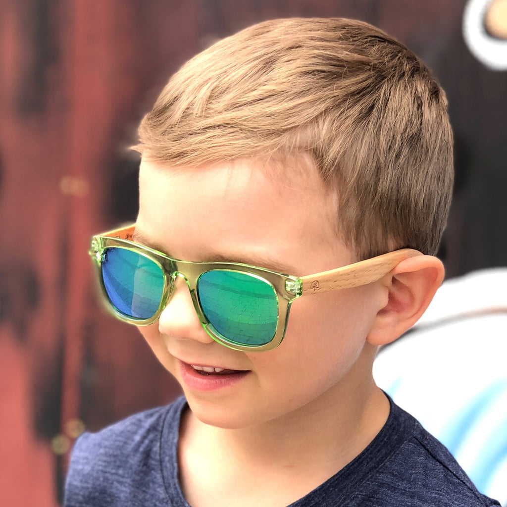 Kid wearing Wildwood kids' polarized sunglasses with recycled plastic frames and solid beech wood arms.