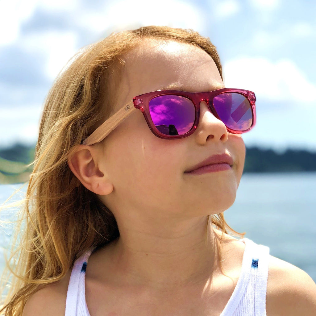 Girl wearing Wildwood kids' polarized sunglasses with recycled plastic frames and solid beech wood arms. Colour Pink.