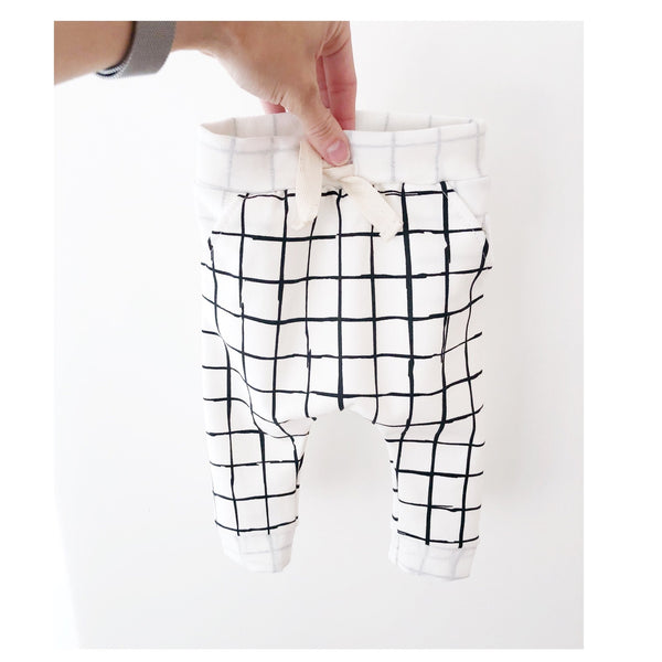 Kids white trousers with black grid. Made of 92% organic cotton 8% spandex French Terry