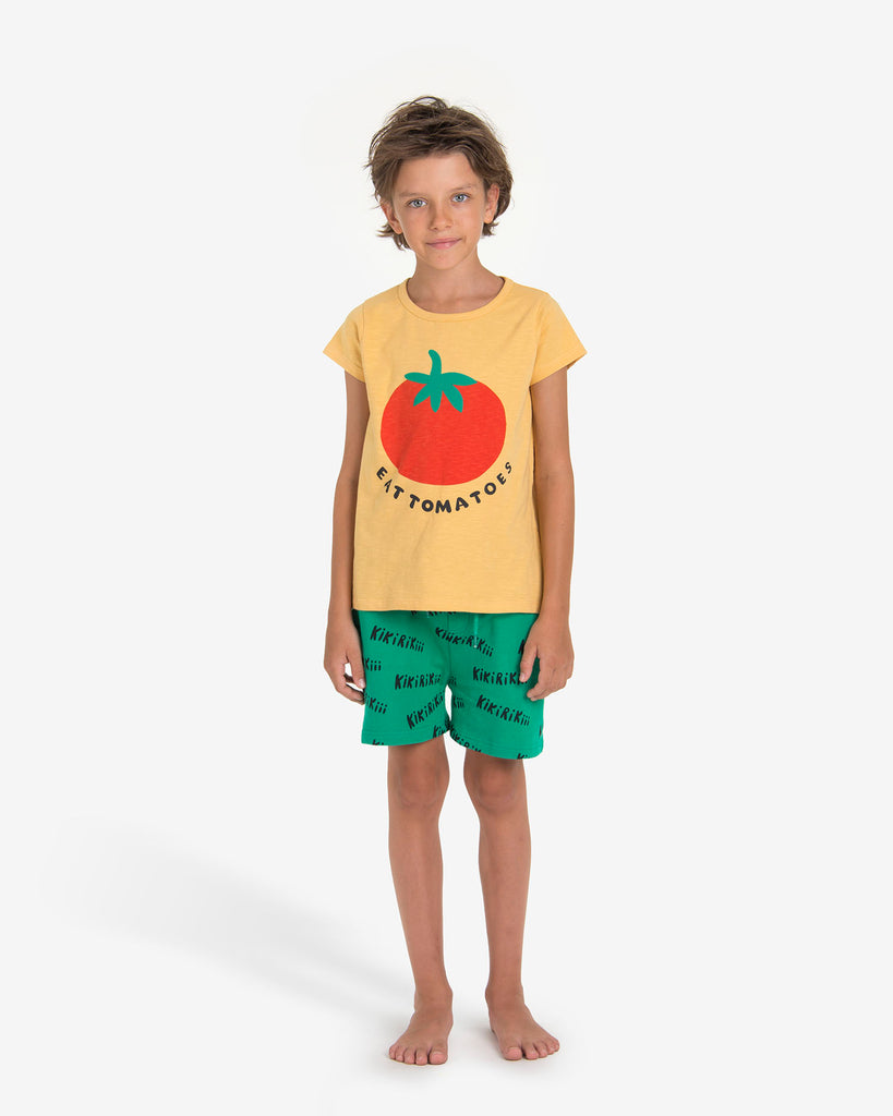 "Boy wearing Nadadelazos Green short with two side pockets and adjustable waistband. ""Kikirikiki"" print all over (This is what roosters say in Spanish). Ethically made in India with 100% certified organic cotton."
