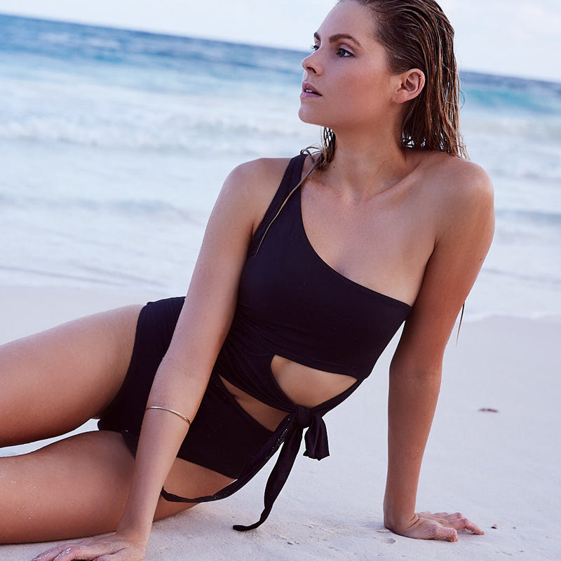 girl on beach wearing black one piece swimsuit with cut out detail and tie