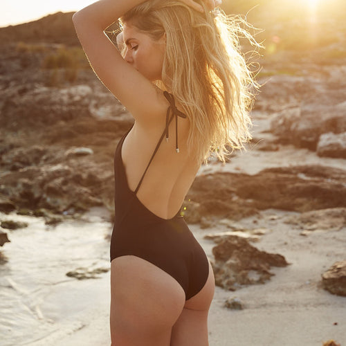 girl on the beach wearing black one piece swimsuit with changeable straps