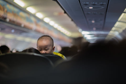 Baby Peeking over Airplane Seats
