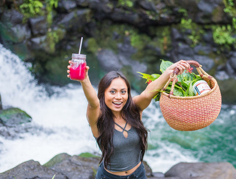 Energetic girl holding basket and Light Up in front of waterfall on Kauai