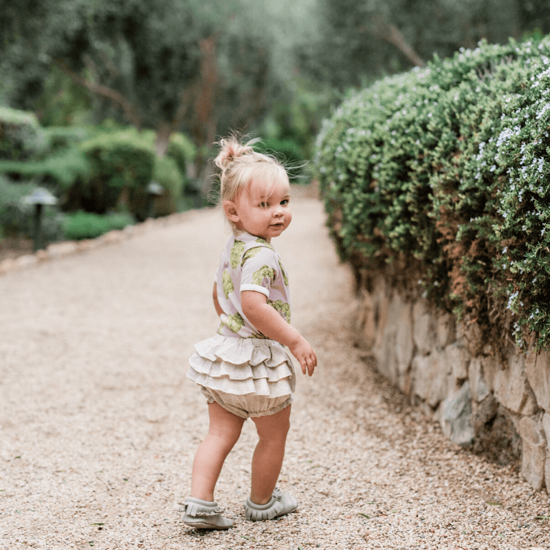 toddler girl wearing milkbarn outfit featuring artichoke one-piece