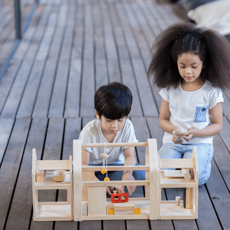 children playing with plantoys slide n go dollhouse