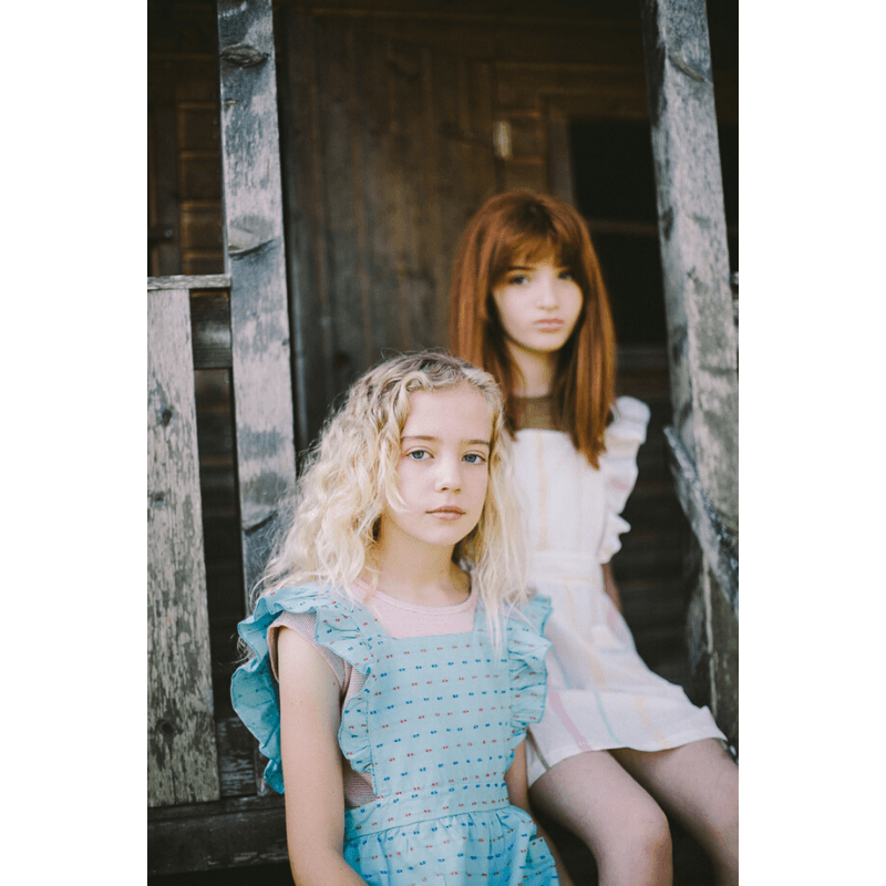girls wearing lia ruffle apron dress