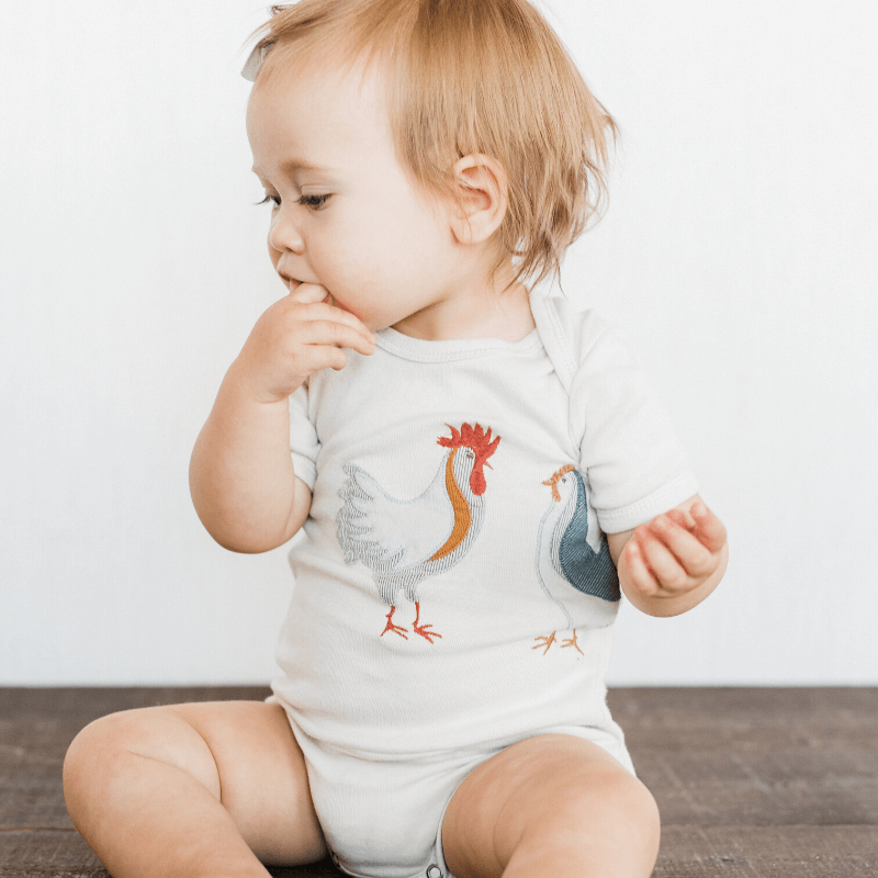 baby wearing applique onesie in chicken
