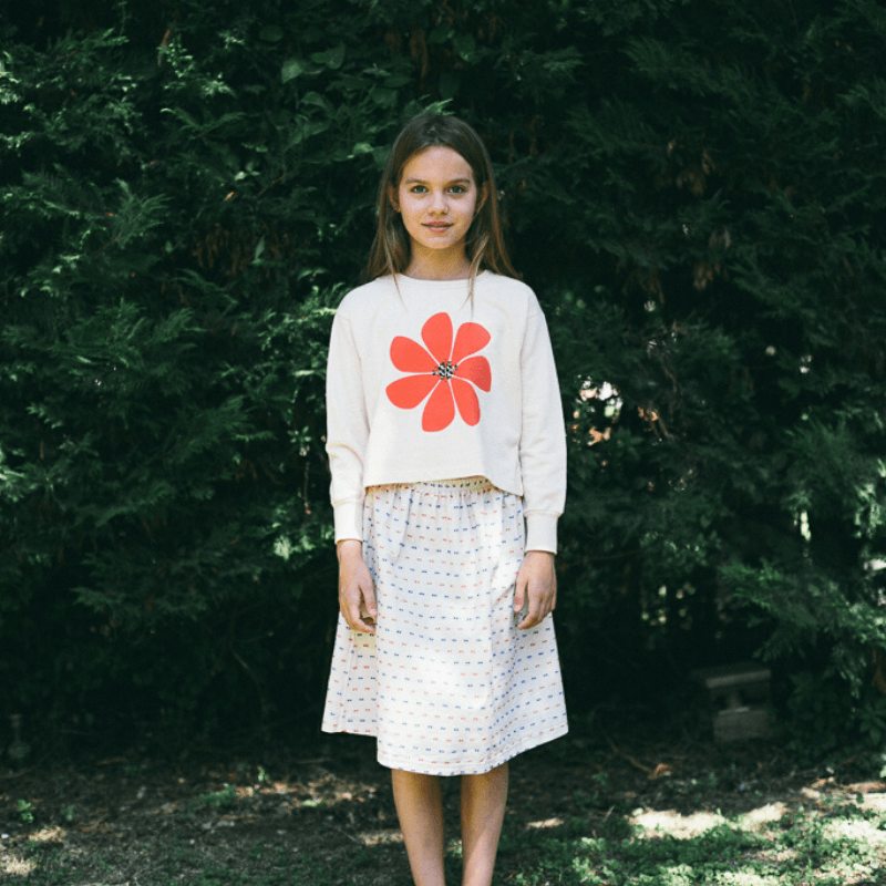 girl wearing picnik cropped flower sweatshirt paired with multi dot skirt
