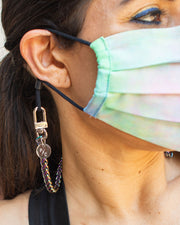 Close up photo of rainbow face mask chain holder worn around neck and ear