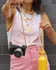 Gold long braided Nikki chain shown as a camera strap and water bottle holder