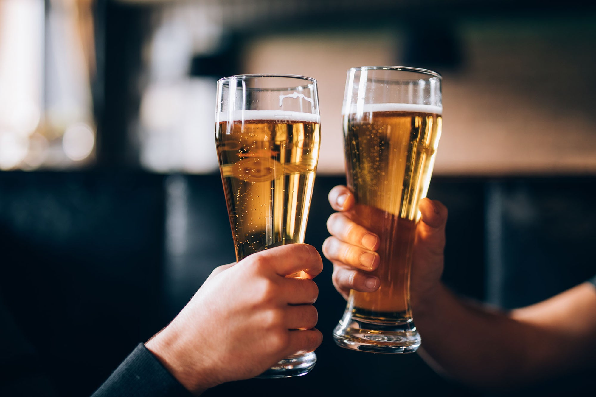 Two people holding up full beer glasses