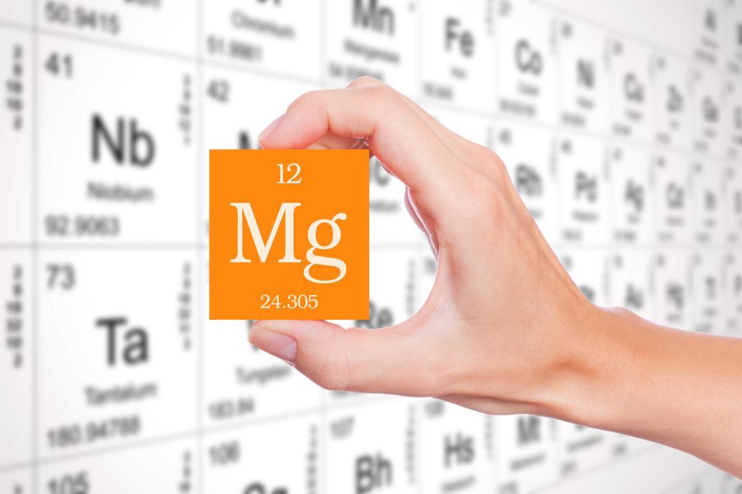 Hand holding a symbolic magnesium block on the periodic table