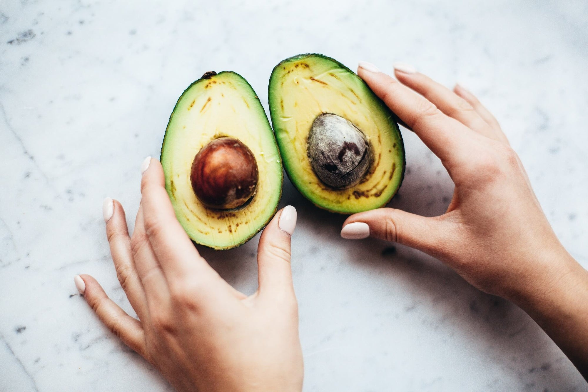 Hands holding a healthy avocado sliced in half