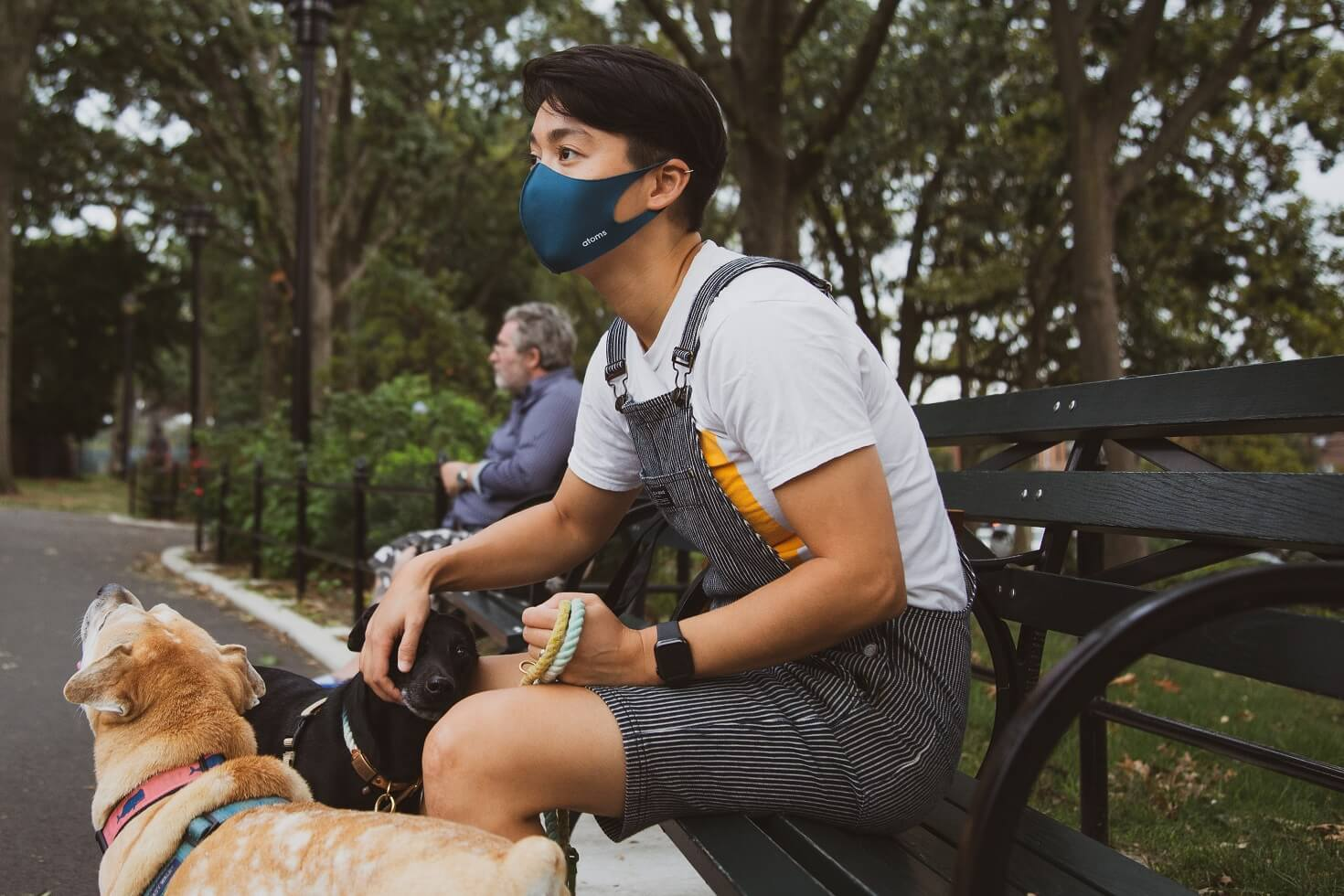 Man wearing mask in the park with his dog during Covid-19