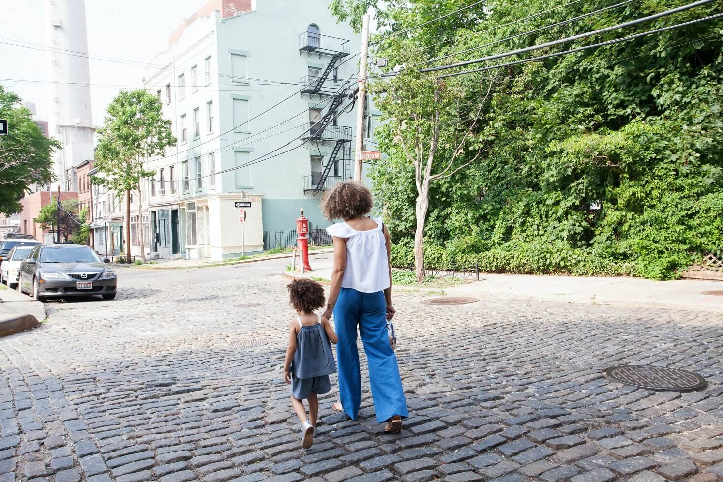 Mom and young daughter walking down the street holding hands