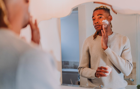 a man stands in a bathroom looking in the mirror and putting moisturizer on his face