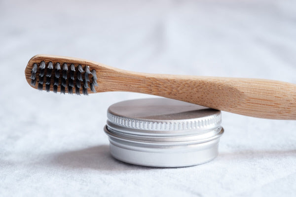 Toothbrush with black bristles on a tin of probiotic toothpaste