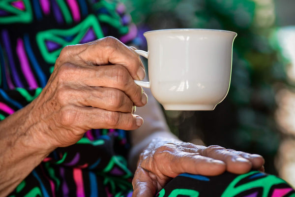 Elderly woman's hands holding a cup of coffee