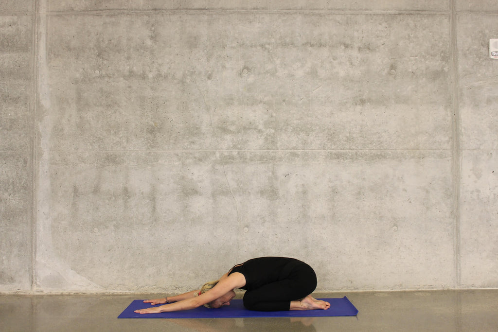 Woman doing yoga in a concrete room