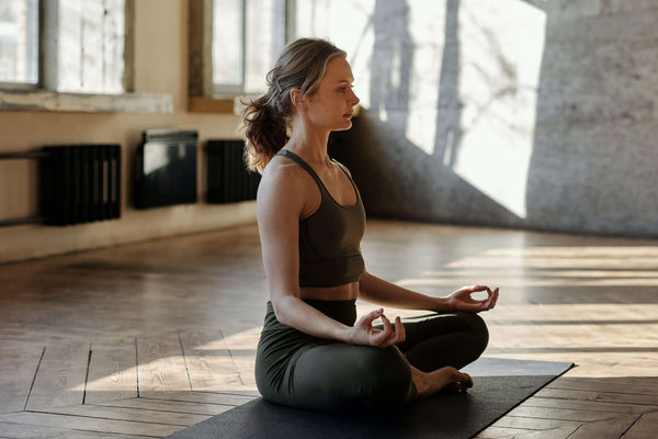 Woman sitting with legs crossed on yoga mat