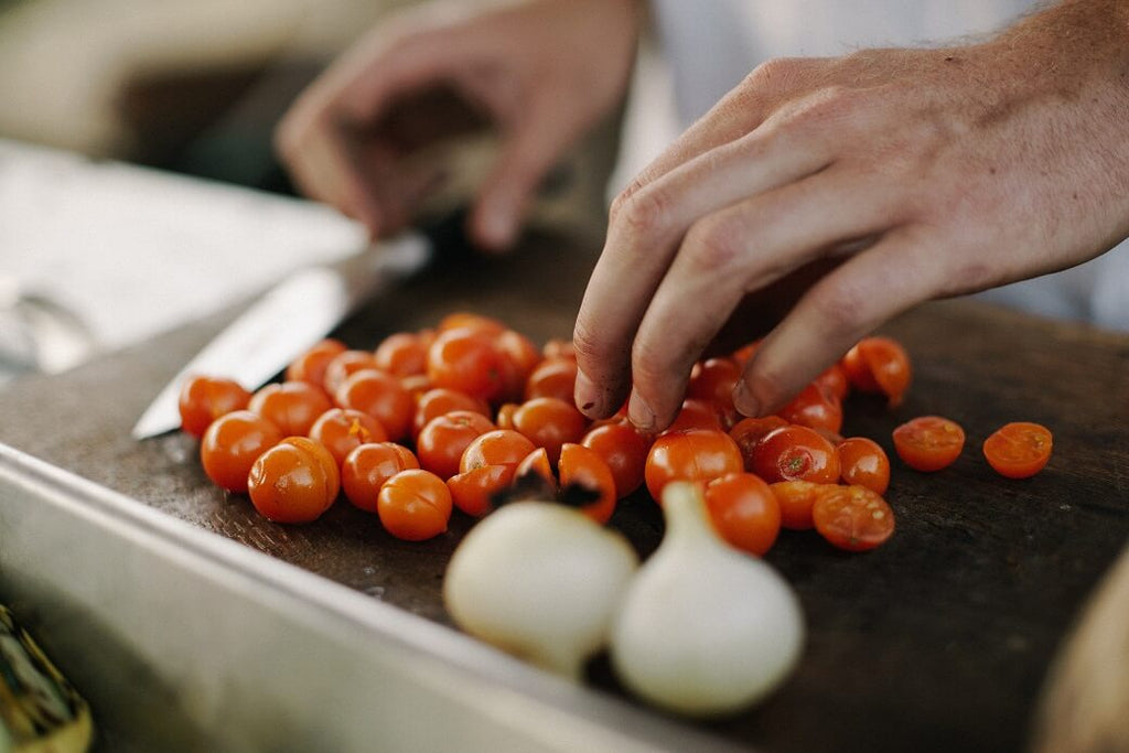 Person cutting cherry tomatoes and garlic on a cutting board