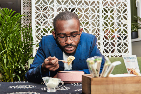 A man in a suit blows on the food on his fork as he raises it to his mouth