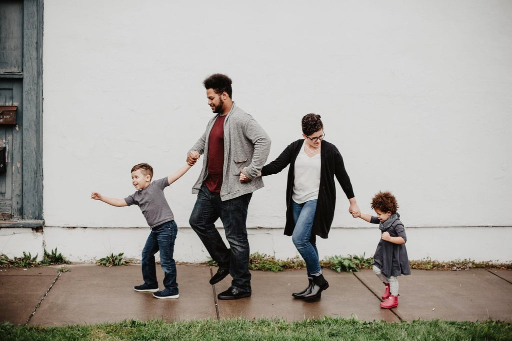 Family of four walking on the sidewalk holding hands