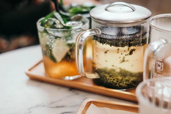 Pitcher of hot green tea and a glass of sparkling tea