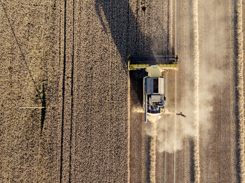 a bird's eye view of a tractor in a field and a bird flying next to it